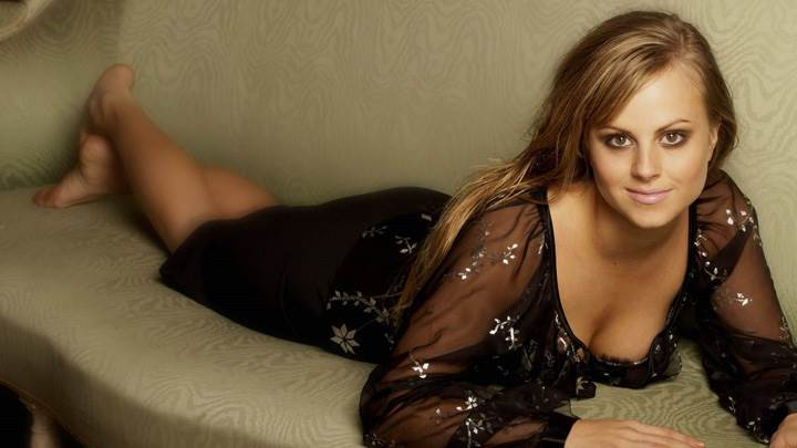 Tina O'Brien Smiling in Black Dress Laying Pose On Sofa